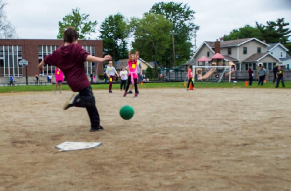 Eagle Point student kicking a kickball.