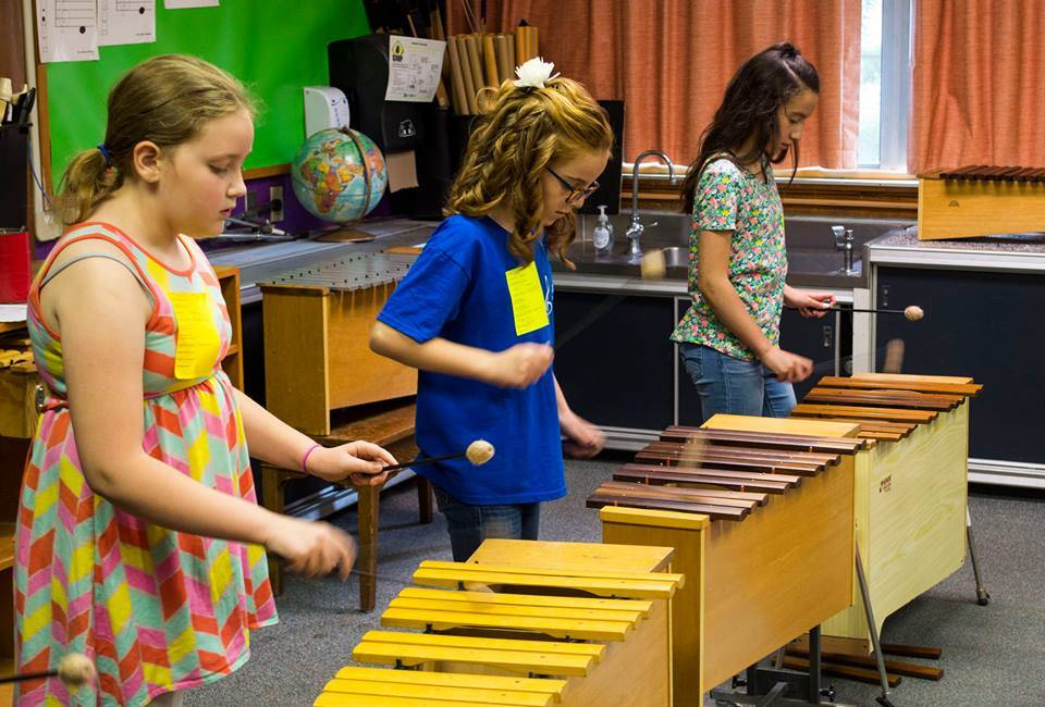 Students playing a musical instrument.