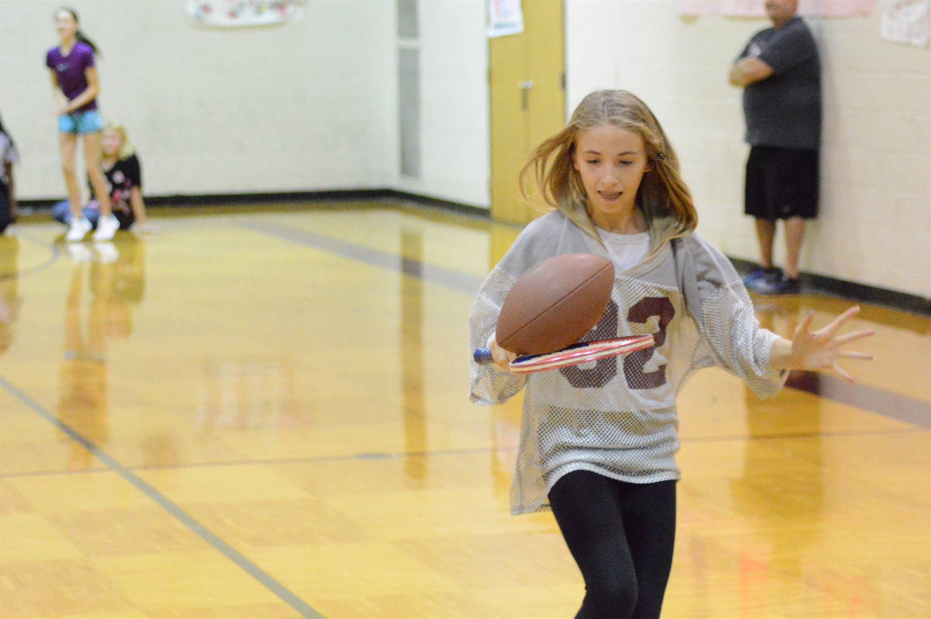 Student running with a tennis racket holding a football during an assembly.