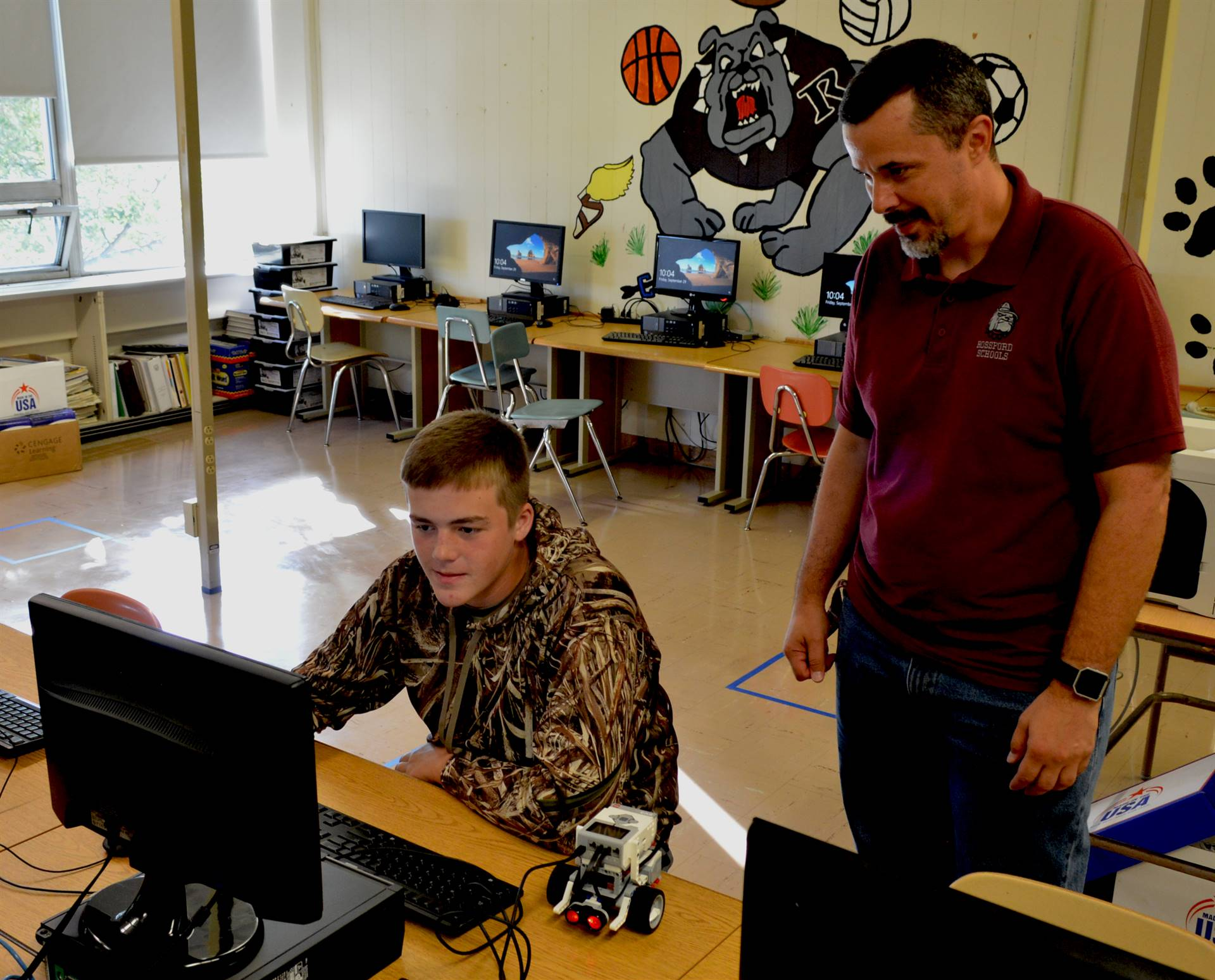 Student and teacher working on a computer program during STEM class.