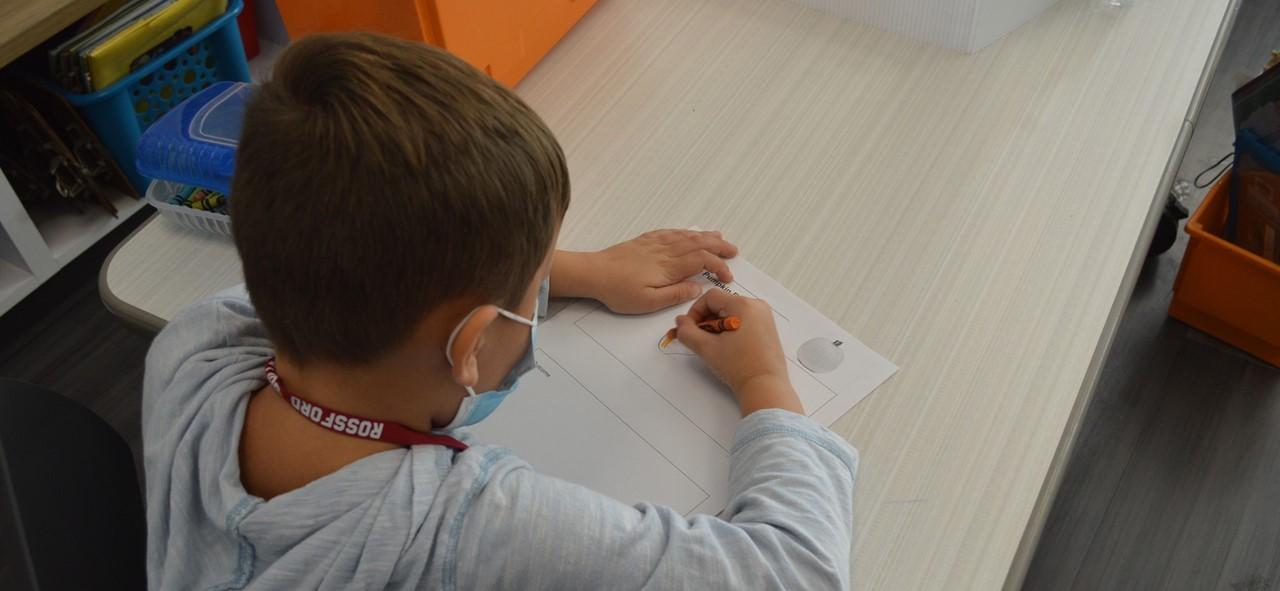 Kindergartner working at his desk.