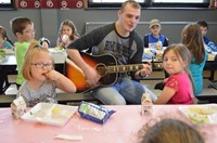 Instructor playing guitar for students at CLC meal