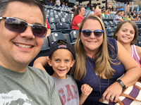 Mark Swavel at Toledo Mud Hens game with his wife and two children